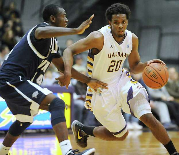 Gerardo Suero of UAlbany is guarded by Patrick Konan, left, of New Hampshire as he drives to the bas