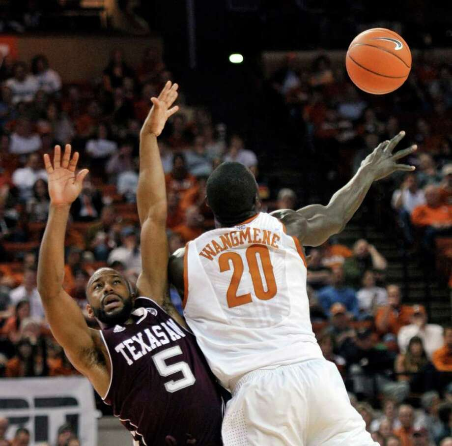 Texas A&M guard Dash Harris (5) defends as Texas forward Alexis Wangmene (20) tries to pass the ball during the first half of an NCAA college basketball game Wednesday, Jan. 11, 2012, in Austin, Texas. (AP Photo/Michael Thomas) Photo: Michael Thomas, Associated Press / FR65778 AP