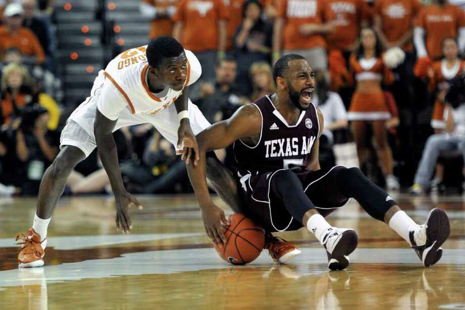 Texas A&M guard Dash Harris, right, fights for a loose ball with Texas guard Myck Kabongo during the first half of an NCAA college basketball game Wednesday, Jan. 11, 2012, in Austin, Texas. (AP Photo/Michael Thomas) Photo: Michael Thomas, Associated Press / FR65778 AP