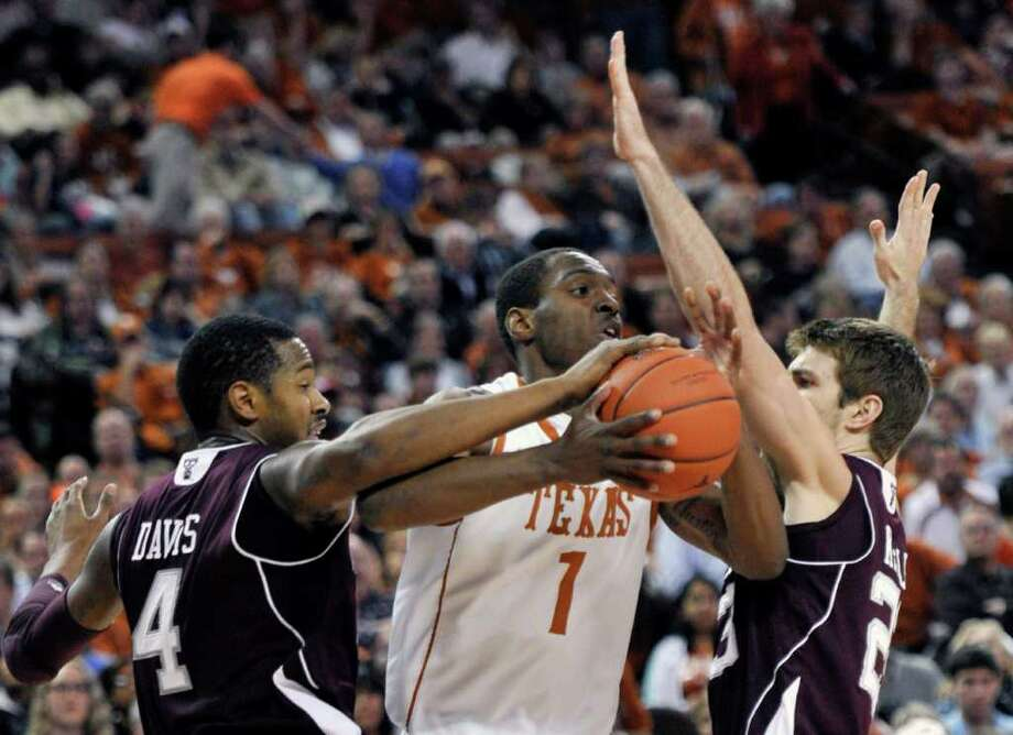 Texas guard Sheldon McClellan works between Texas A&M center Keith Davis, left, and guard Zach Kinsley during the first half of an NCAA college basketball game Wednesday, Jan. 11, 2012, in Austin, Texas. (AP Photo/Michael Thomas) Photo: Michael Thomas, Associated Press / FR65778 AP