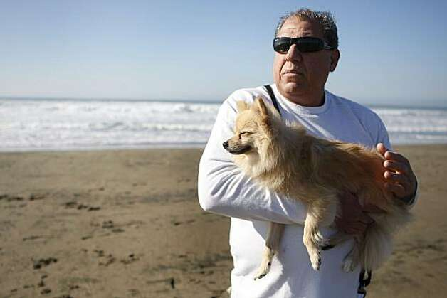 Ellsworth Miller holds his dog Hula on Ocean Beach, part of the Golden Gate National Recreation Area in San Francisco Calif. on Friday, Jan. 21, 2011. Miller says that Ocean Beach is the only place he feels safe letting Hula off her leash. Photo: Alex Washburn, The Chronicle