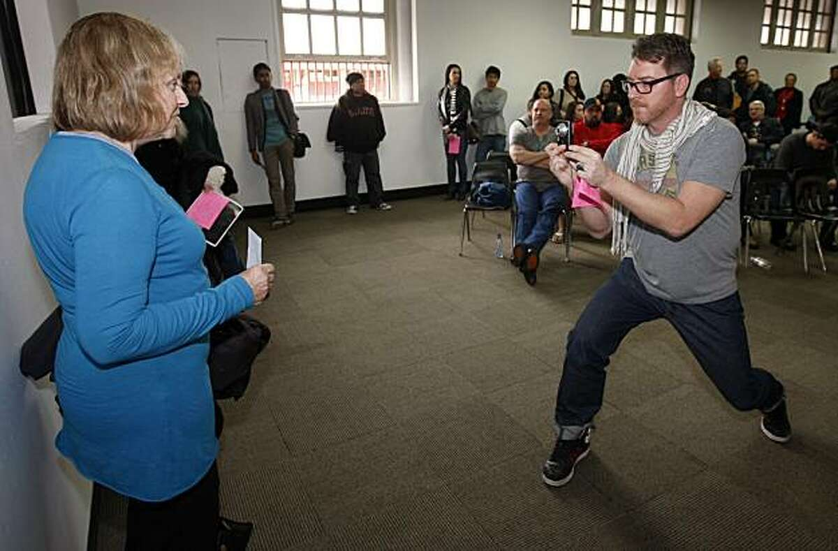 Cody Bayne (right) shoots a photo of Aurelia Fort, who was among the hundreds of aspiring actors who waited in line for a casting call at Fort Mason on Saturday, hoping to land a part as an extra in the upcoming film