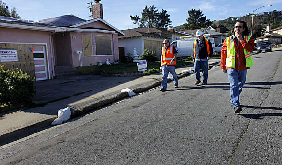Marty Medina, right, a public works inspector with the City of San Bruno, escorts inspectors from PG&E through the  neighborhood that was affected by the pipeline blast, Thursday January 20, 2011, in San Bruno, Calif. The inspectors are looking to redirect power lines to some of the homes. Photo: Lacy Atkins, The Chronicle