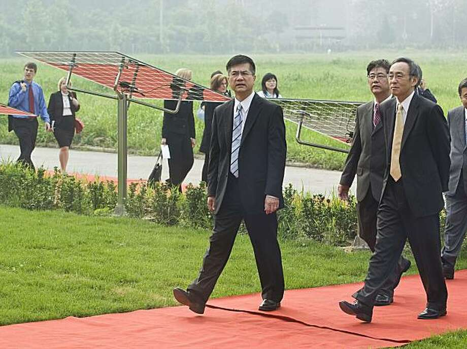 U.S. Secretary of Energy Stephen Chu, right, and Commerce Secretary Gary Locke, center, visit a Solar-Powered Future House, a clean energy residential development project in Beijing, China, Thursday, July 16, 2009. Both Chu and Locke were in Beijing to lobby China to promote private-sector development of solar, wind, biofuels and other clean energy. (AP Photo/Andy Wong) Photo: Andy Wong, AP