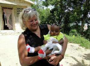Cindy Schmehl, executive director of To Love a Child, holds a Haitian during an Aug. 2011 visit to Haiti. ( Photo courtesy Cindy Schmehl)