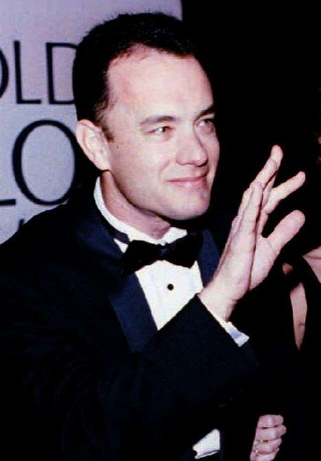 "BEVERLY HILLS, CA - JANUARY 23:  US actor Tom Hanks (L), with his wife, Rita, waves to photographers as they arrive for the 51st Golden Globe Awards 22 January 1994 in Beverly Hills, CA. Hanks won the best actor in drama award for his role in the film ""Philadelphia.""  (Photo credit should read DAVID CRANE/AFP/Getty Images) Photo: David Crane"