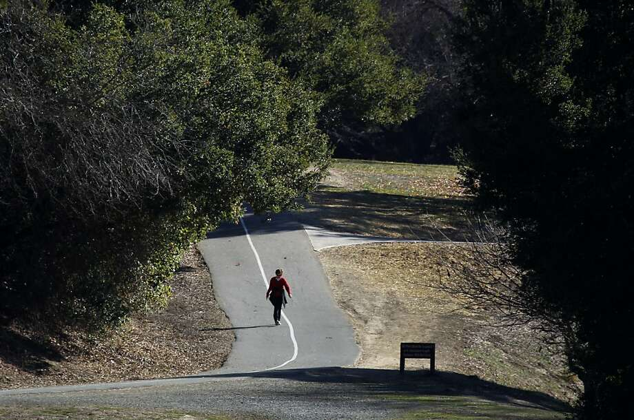 A woman walks on a trail past drier than normal terrain at the Lafayette Reservoir Recreation Area in Lafayette, Calif. on Wednesday, Jan. 11, 2012. Bay Area residents continue to bask in spring-like conditions but forecasters are hoping a rainy pattern may finally return to the region next week. Photo: Paul Chinn, The Chronicle
