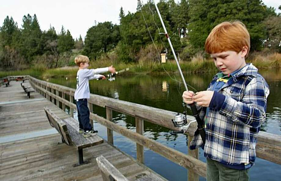 Aden Kovach( left) casts his line as Jack Phillips  baits his hook on the dock at the Lafayette Reservoir Wed. Feb. 18, 2009, in Lafayette, Calif. Photo: Lacy Atkins, The Chronicle