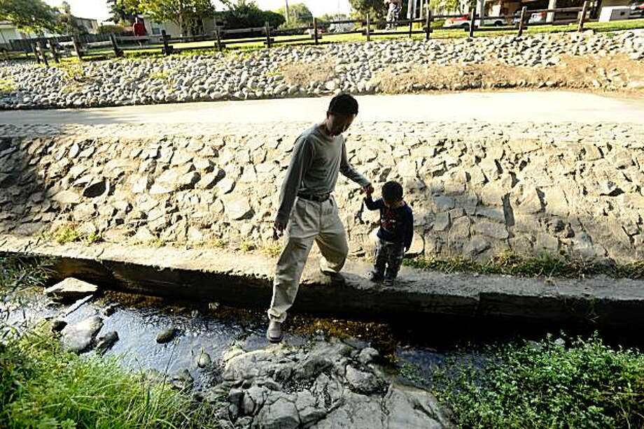 Ren Xu crosses Cerrito Creek with his son Tony Xu, 2, on Friday, Aug. 15, 2008, in El Cerrito, Calif. Photo: Noah Berger, Special To The Chronicle