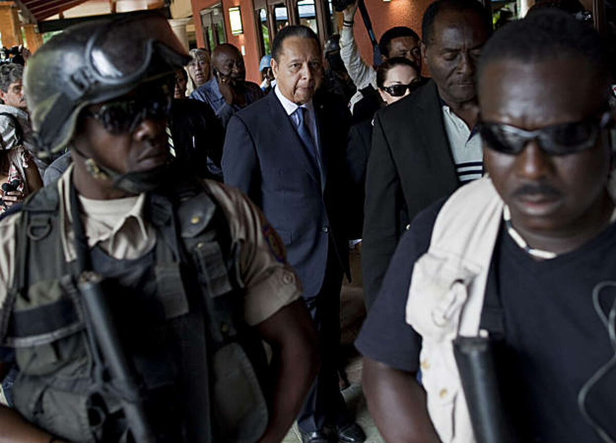 Police officers take ex-dictator Jean-Claude Duvalier, center back, out of his hotel in Port-au-Prince, Haiti, Tuesday Jan. 18, 2011. Haitian police took Duvalier, who abruptly returned to Haiti on Sunday, out of his hotel to a waiting SUV without sayingwhether he was being detained for crimes committed under his brutal regime.