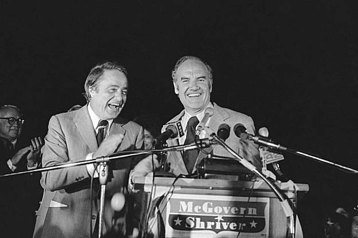 Sargent Shriver left, leads the applause after introducing Sen. George McGovern to a crowd at Austin?s Municipal Airport at night, Monday, August 22, 1972. The Democratic presidential and vice presidential candidates met in Austin for a planned visit with former President Lyndon B. Johnson at the LBJ Ranch in morning on Tuesday. (AP Photo/Ted Powers)