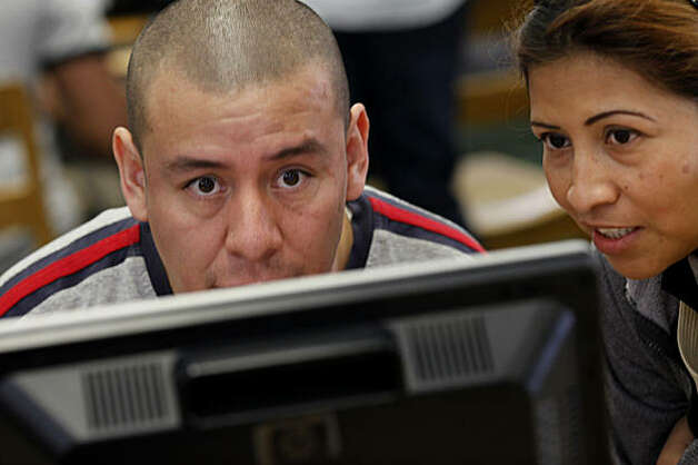 Carlos Gonzales (center) and his wife Maria worked on a computer at the library to complete their Section 8 application. The Oakland Housing Authority and Oakland public library are working to provide computer access to low income families, the elderly and disabled who are interested in applying for Section 8 housing Tuesday January 25, 2011. Photo: Brant Ward, The Chronicle