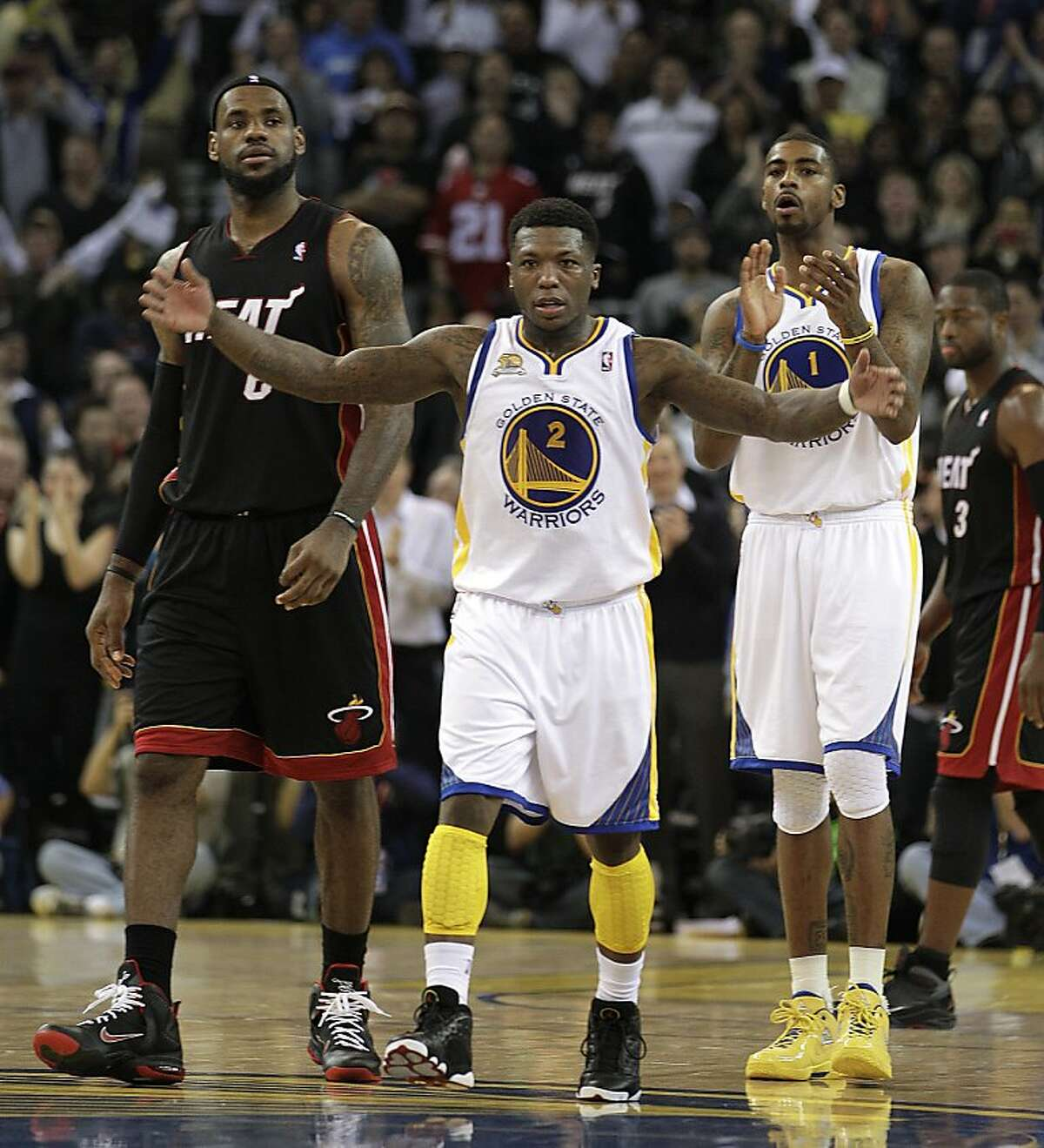 Golden State Warriors' Nate Robinson (2) and Dorell Wright (1) celebrate as Miami Heat's LeBron James, left, and Dwyane Wade (3) look on during the fourth period of an NBA basketball game Tuesday, Jan. 10, 2012, in Oakland, Calif. (AP Photo/Ben Margot)