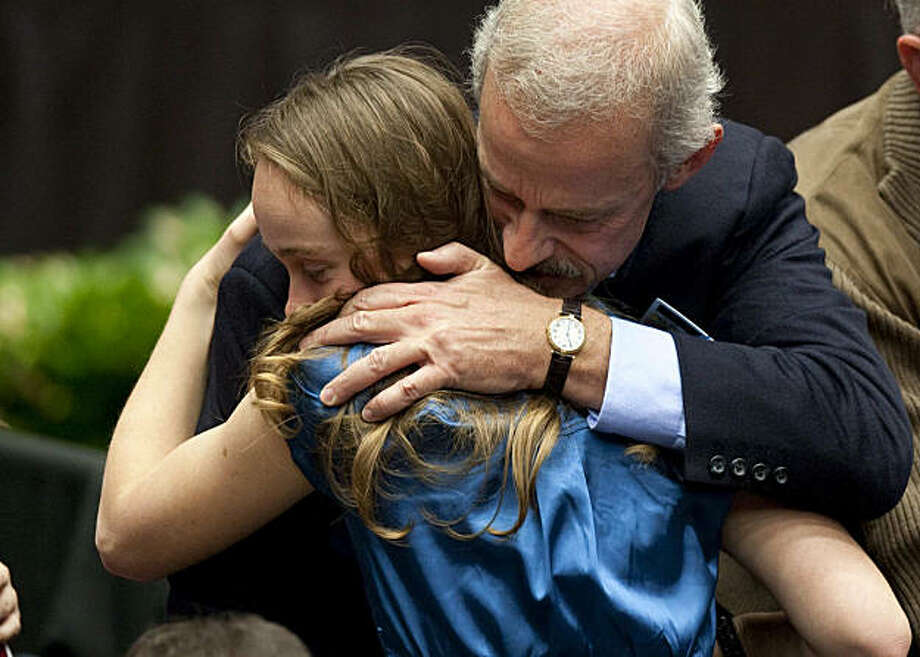 """Bill Hileman, whose wife Susan brought 9-year-old Christina Taylor Green to meet Rep. Gabrielle Giffords (D-Ariz.), hugs a family member during the """"Together We Thrive"""" program honoring the victims of the shooting in Tucson, Arizona, Sunday, January 16, 2011. Christina was killed during the shooting and Susan wounded. (Gina Ferazzi/Los Angeles Times/MCT) Photo: Gina Ferazzi, MCT"""
