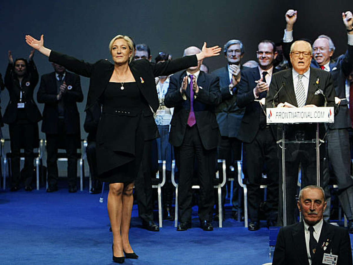 Marine Le Pen reacts after her election as leader of the French far right party National Front during their national congress in Tours, western France, Sunday, Jan. 16, 2011. Le Pen, the 42-year-old daughter of far-right firebrand Jean Marie Le Pen, seen at lectern at right, won slightly more than two-thirds of the vote in an election for its new president. The 82-year-old party founder bid his farewell Saturday with an impassioned defense of his polemic anti-immigration, anti-Islam platform. He created the party in 1972. A mother of three, Marine is widely seen as the kinder, gentler face of a party known for its extreme stances.