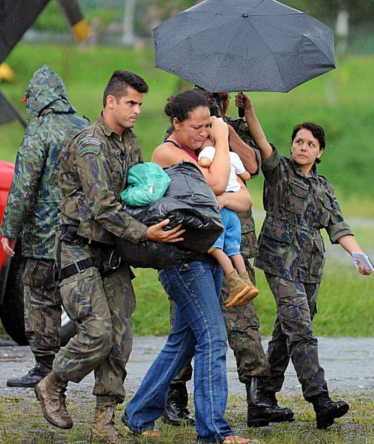 Brazilian Air Force members help a woman who was rescued with her children at a temporary air base in Itaipava, Petropolis, some 100 km from downtown Rio de Janeiro, Brazil, on January 17, 2011. The death toll from devastating floods and landslides in Brazil rose Monday to 640, as the military stepped up efforts to reach isolated communities near Rio.