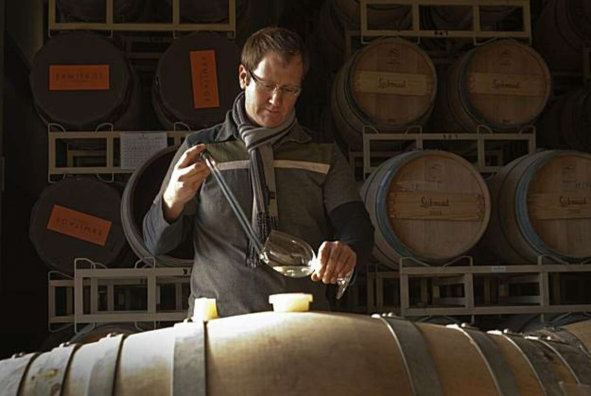 Massican winemaker Dan Petroski takes a sample from a barrel of his wine for tasting Monday, Jan. 3, 2011 in Calistoga.