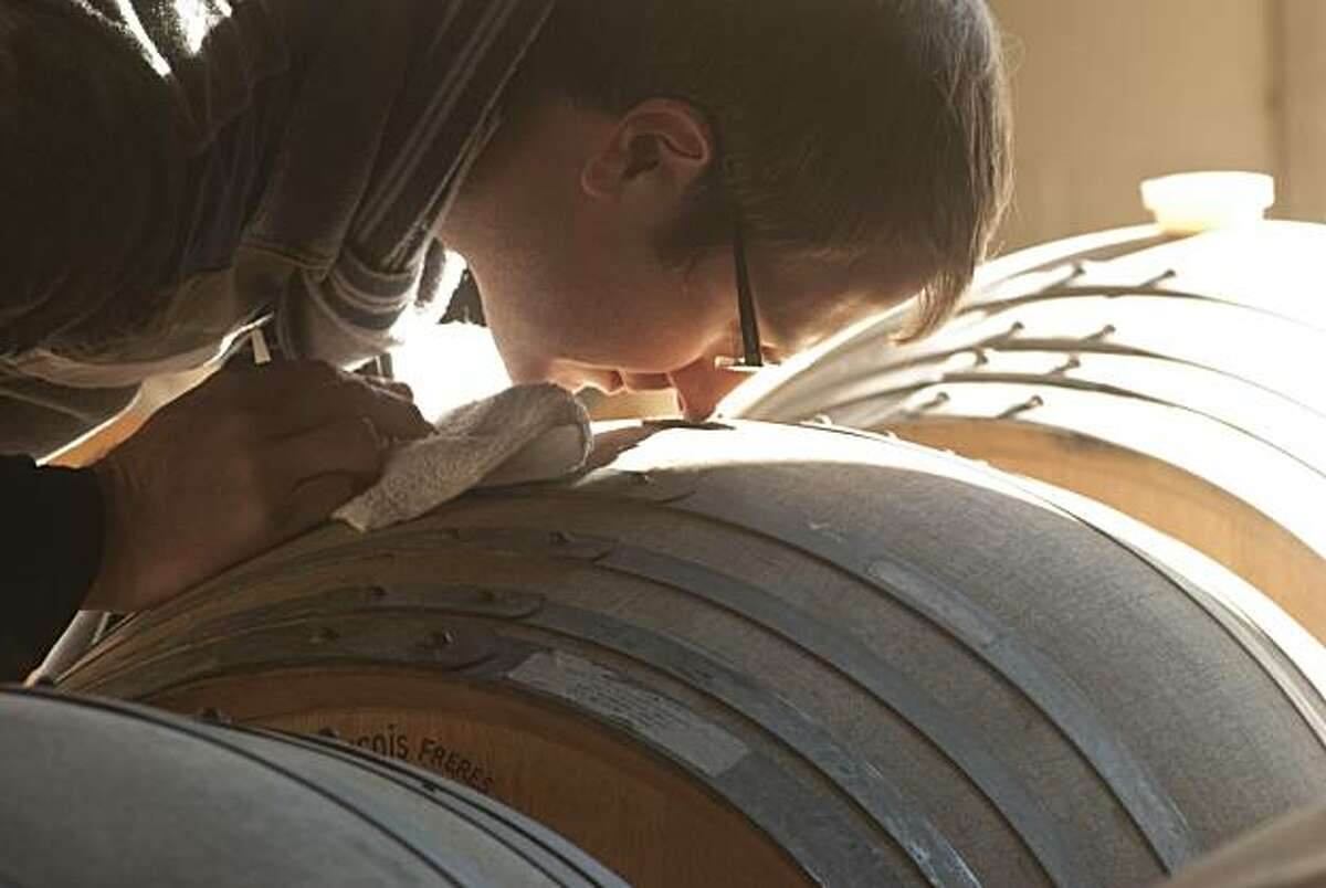 Massican winemaker Dan Petroski takes a sniff from a barrel of his wine Monday, Jan. 3, 2011 in Calistoga.