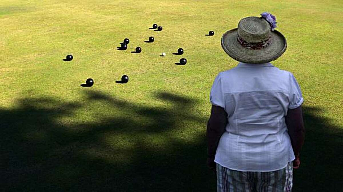 Bocce - 9:45 a.m. - Oakland. I stopped to watch as the Oakland Lawn Bowling Club played a few games at Lake Merritt Park. I liked the hat one of the players was wearing as she watched her partner bowl. Camera settings: Canon 5D MkII, ISO 200, 1/1000, f6.3, 32mm lens.