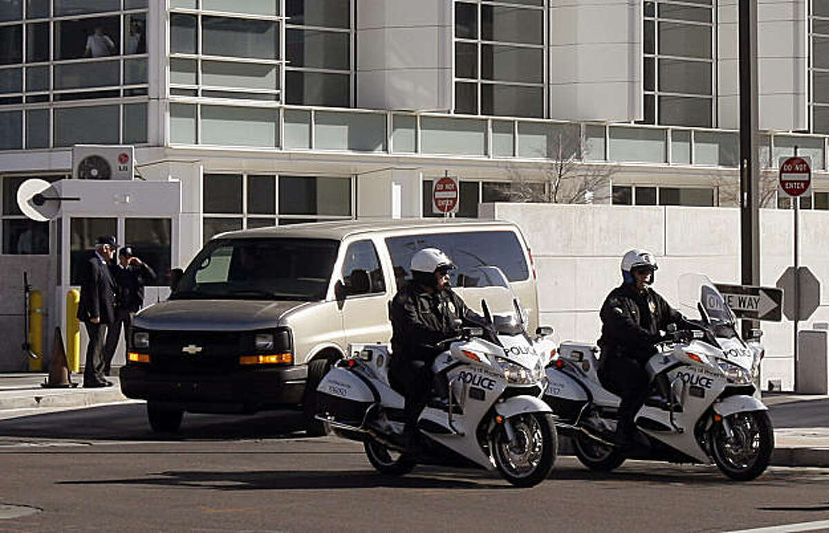 Under police escort, U.S. Marshals leave in a van, back, with Jared Loughner, the man accused of carrying out a mass shooting in Tucson, who pleaded