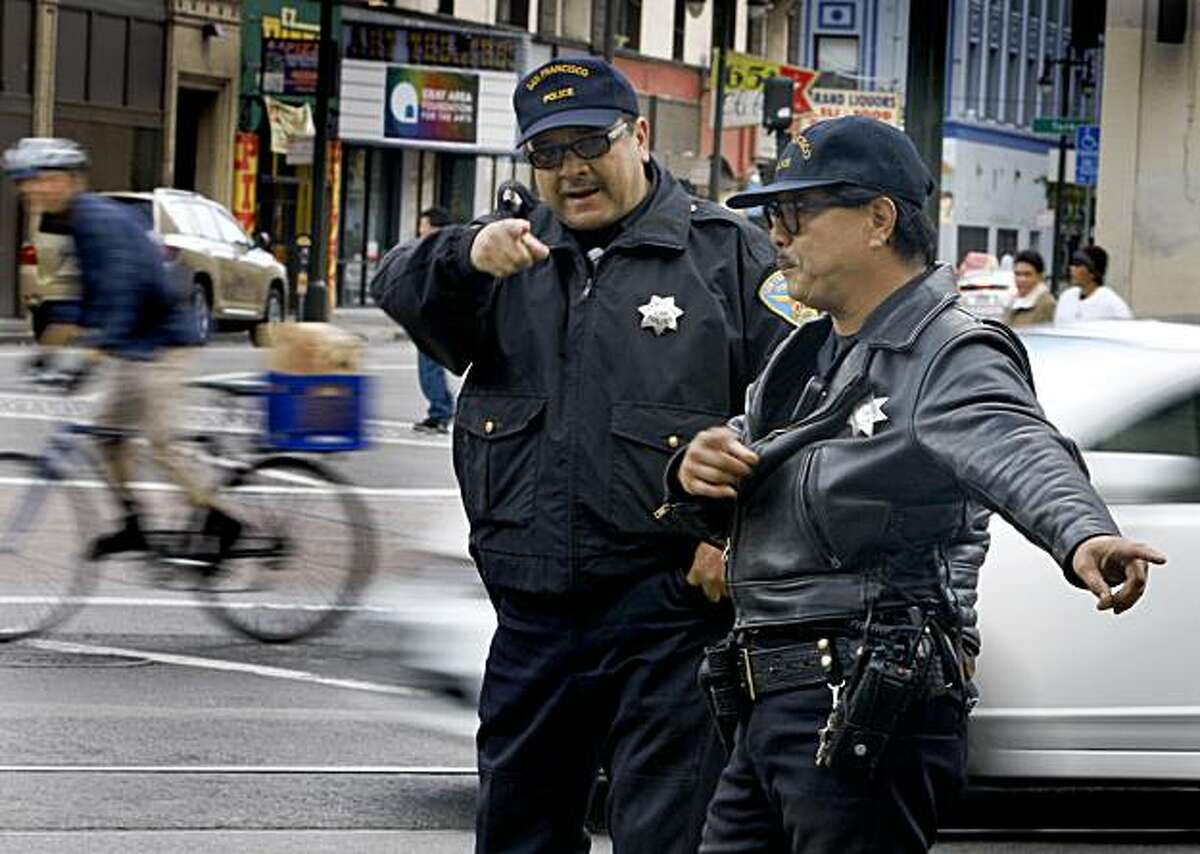 Police officers direct traffic on eastbound Market Street to turn right at Sixth Street in San Francisco on Tuesday.