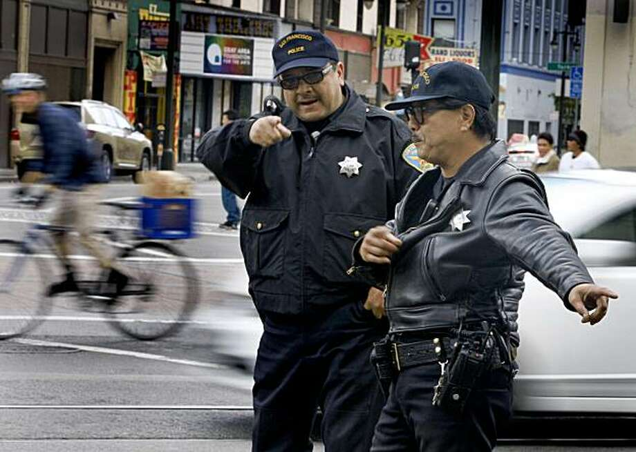 Police officers direct traffic on eastbound Market Street to turn right at Sixth Street in San Francisco on Tuesday. Photo: Paul Chinn, The Chronicle
