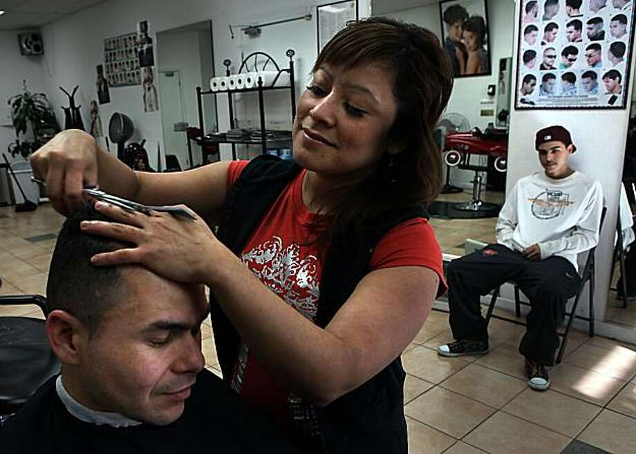 Barber Milagro Leon Rivas working on Neybar Orellana at Chica Sexy in the mission district in San Francisco, Calif., on Wednesday, January 19, 2011.  Orellana has been her customer for 7 years.  Growing up in El Salvador, Rivas used to cut hair out of her garage for $1.50 a head. Photo: Liz Hafalia, The Chronicle
