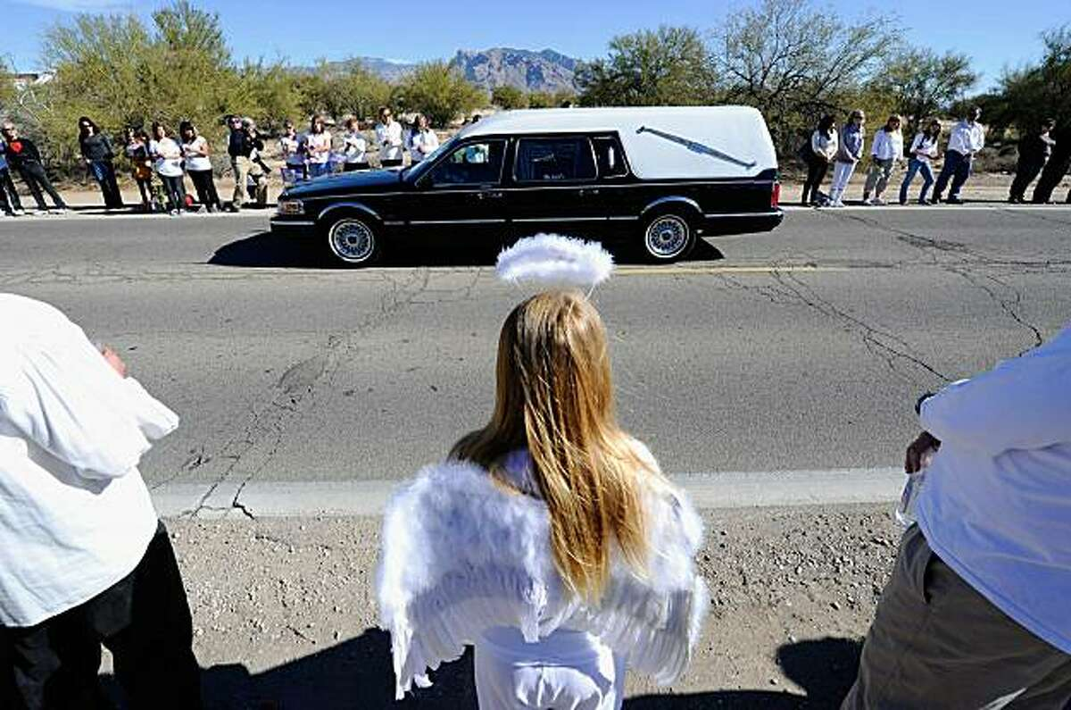 TUCSON, AZ - JANUARY 13: Lindsey Lummus (C), 10, wearing an angels wings and a halo, watches as the funeral hearse carrying the casket of nine-year-old Christina Taylor Green arrives at St. Elizabeth Ann Seton church on January 13, 2011 in Tucson, Arizona. Green was shot and killed during the January 8, shooting rampage of Jared Lee Loughner during a political event in Tucson. (Photo by Kevork Djansezian/Getty Images) ***BESTPIX***