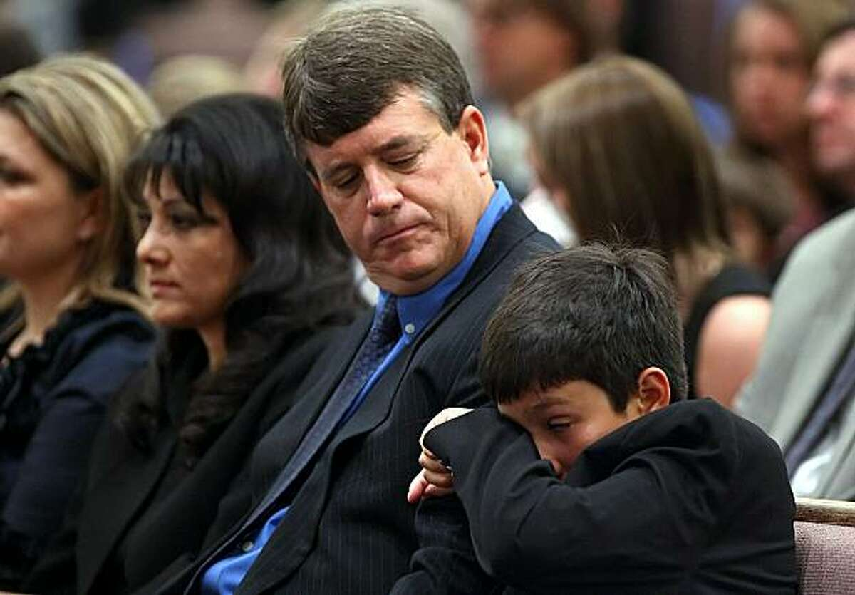 TUCSON, AZ - JANUARY 13: (L to R) Brother Dallas Green wipes away a tear while seated next to his father John Green and mother Roxanna Green during the funeral service for their daughter nine-year-old Christina Taylor Green at St. Elizabeth Ann Seton church on January 13, 2011 in Tucson, Arizona. Green was shot and killed during the January 8, shooting rampage of Jared Lee Loughner during a political event in Tucson.