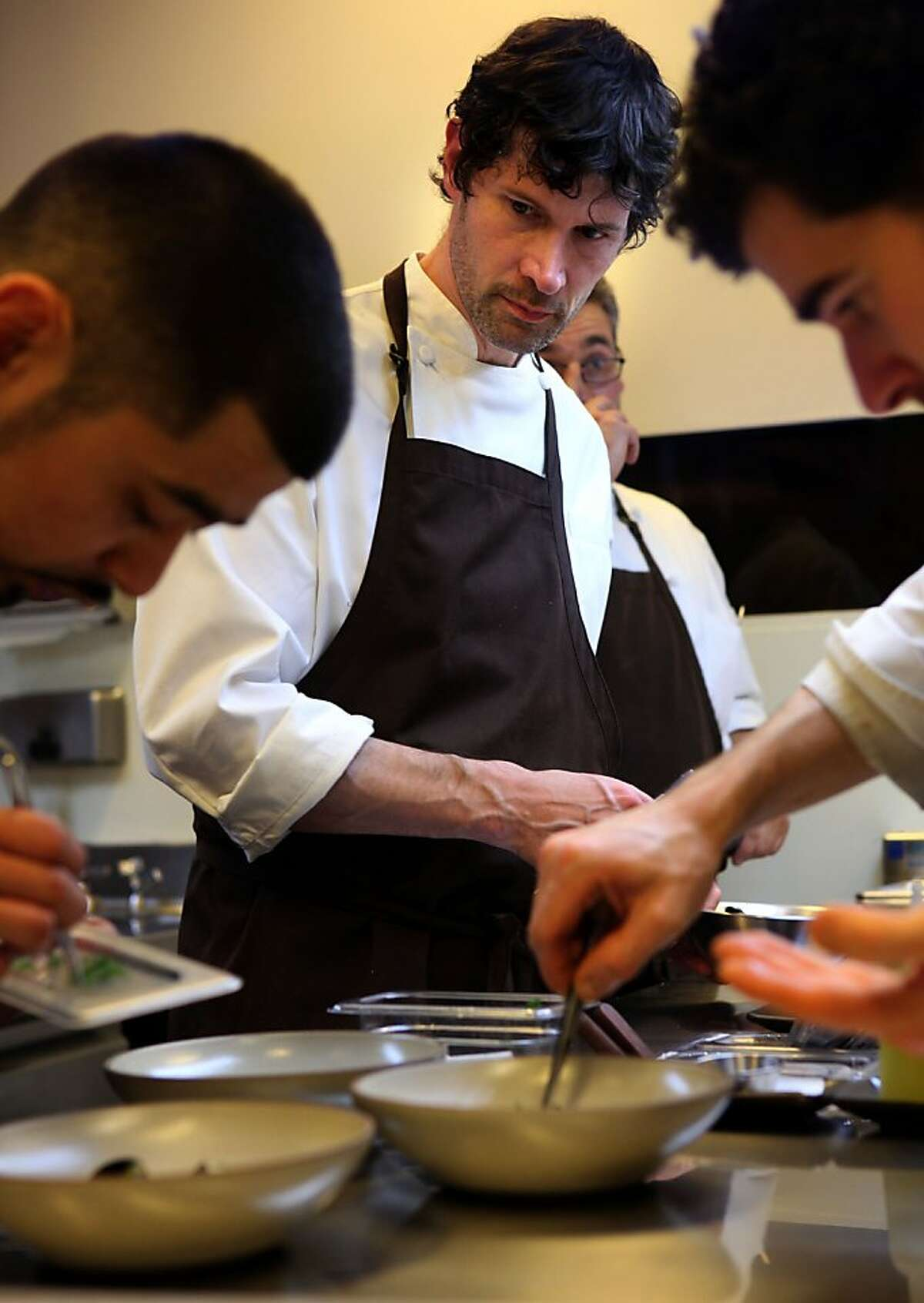 Four-star chef Daniel Patterson of Coi keeps watches his chefs while plating dishes.