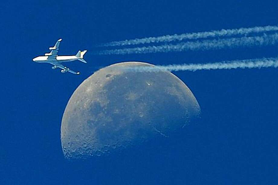 A commercial plane, a Boeing 747 flying in front of the moon on September 30, 2010 is seen from Martigues, close to Marseille, southern France, 30 September 2010. Photo: Gerard Julien, AFP / Getty Images