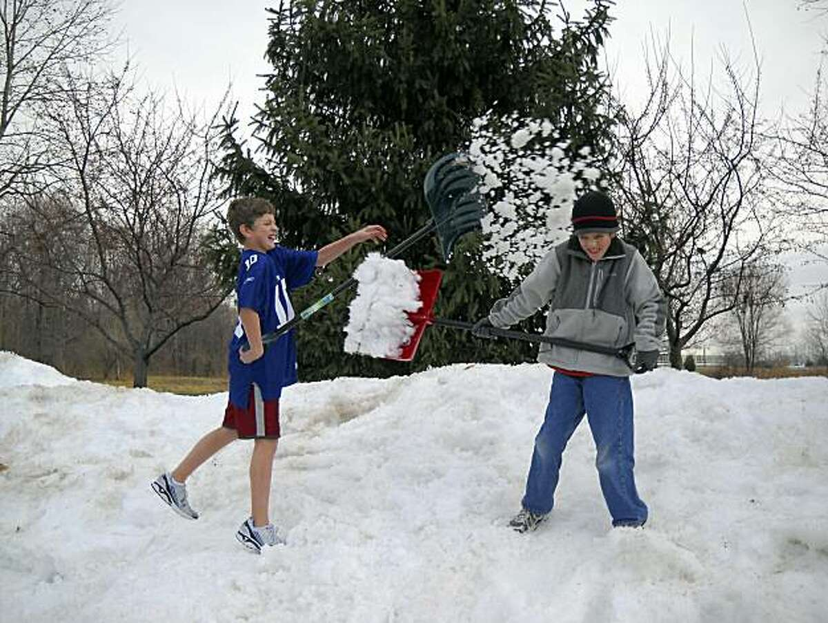 This Thursday, Dec. 30, 2010 photo courtesy of Shelley Rogers Landes shows her sons Jack Rogers, 12, left, and Maxwell Rogers, 9, as they play on a mound of snow in Fishers, Ind. No coat, no gloves, no prob! Some teens and tweens are chillin' out, literally and figuratively, in their sweatshirts and kicks. Maybe a boy will accessorize with a baseball cap, and a girl might choose stylish boots _ but nothing weather-proof, please! Some boys even wear shorts year-round, and many parents say they've given up the winterwear fight. (AP Photo/Shelley Rogers Landes) NO SALES