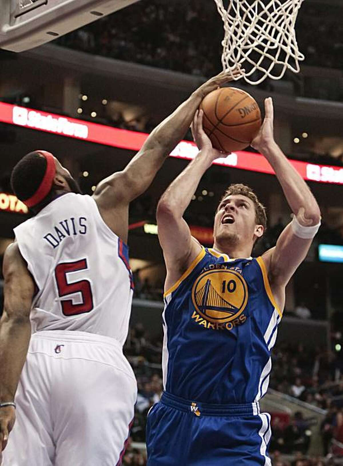 Los Angeles Clippers guard Baron Davis, left, blocks the shot of Golden State Warriors center David Lee during the first half of their NBA basketball game, Saturday, Jan. 22, 2011, in Los Angeles.
