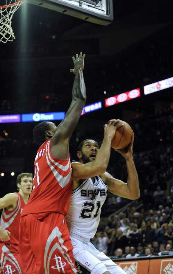 Tim Duncan of the San Antonio Spurs (21) goes up to score the the field game that won the game for the Spurs as Samuel Dalembert of the Houston Rockets defends during the overtime period of NBA action at the AT&T Center on Wednesday, Jan. 11, 2012. BILLY CALZADA / gcalzada@express-news.net