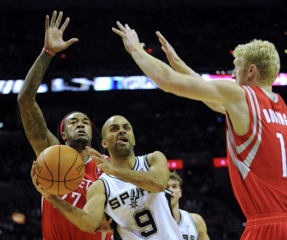 Tony Parker of the Spurs passes off as Jordan Hill, left, and Chase Bodiner of the Rockets defend during first-half NBA action at the AT&T Center on Wednesday, Jan. 11, 2012. BILLY CALZADA / gcalzada@express-news.net