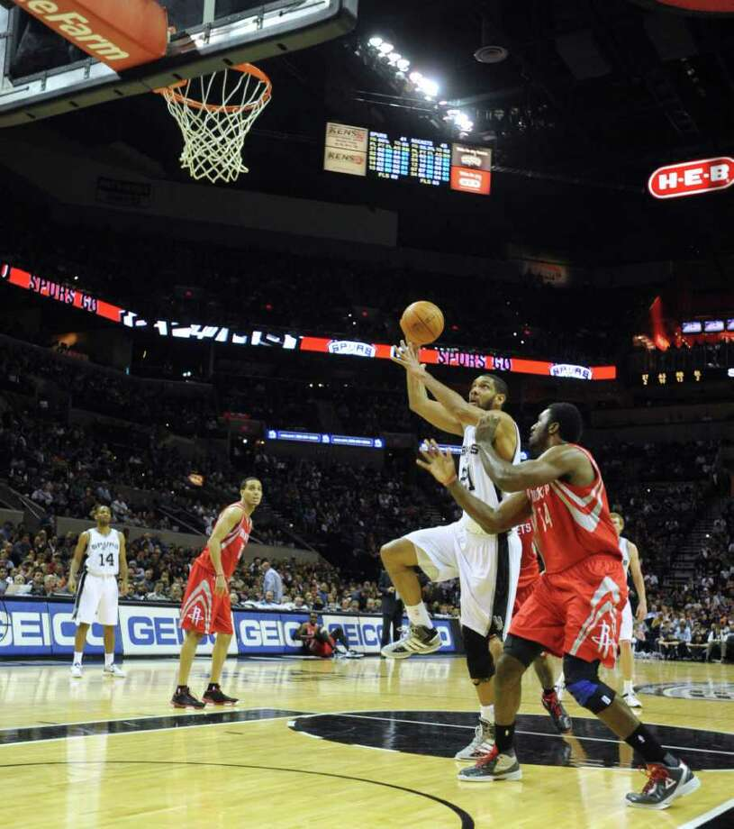 Tim Duncan of the San Antonio Spurs shoots as Patrick Patterson of the Houston Rockets defends during NBA action at the AT&T Center on Wednesday, Jan. 11, 2012. BILLY CALZADA / gcalzada@express-news.net