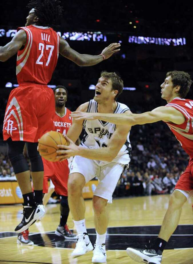 Tiago Splitter of the San Antonio Spurs is fouled by Goran Dragic, right, of the Houston Rockets as he successfully shoots during NBA first-half action at the AT&T Center on Wednesday, Jan. 11, 2012. Splitter was able to make the ensuing free throw. BILLY CALZADA / gcalzada@express-news.net
