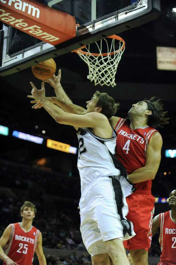 Tiago Splitter of the San Antonio Spurs, in white, is fouled by Luis Scola of the Houston Rockets as he makes a shot during NBA action at the AT&T Center on Wednesday, Jan. 11, 2012. Splitter was able to convert on the ensuing free throw. BILLY CALZADA / gcalzada@express-news.net  Houston Rockets at San Antonio Spurs Photo: BILLY CALZADA, Express-News / gcalzada@express-news.net