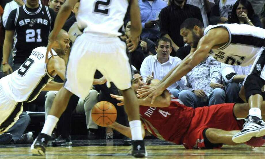 Luis Scola of the Houston Rockets attempts to pass off as Tony Parker, left, and Tim Duncan of the San Antonio Spurs reach for the ball during fourth-quarter NBA action at the AT&T Center on Wednesday, Jan. 11, 2012. BILLY CALZADA / gcalzada@express-news.net  Houston Rockets at San Antonio Spurs Photo: BILLY CALZADA, Express-News / gcalzada@express-news.net