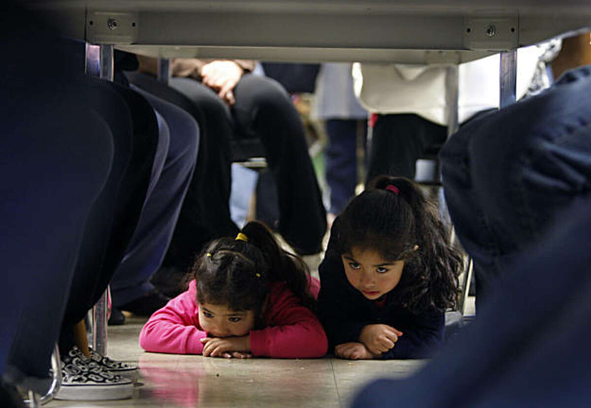 Three-year-old Deanna Villegas (left) spends time under the conference table with her cousin Jacqueline Villegas, 2, while school officials meet with parents to discuss dramatic changes in teacher staffing scheduled to take place in the Fall at Bryant Elementary School in San Francisco, Calif., on Wednesday, Jan. 12, 2011.