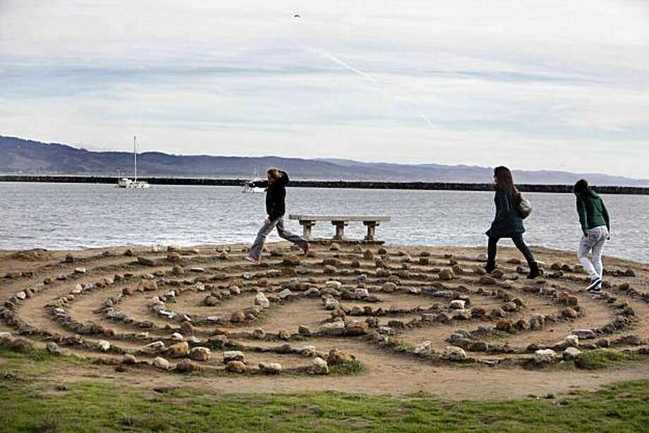 L-R, cousins, Kerry Walker, Katie Herskovitz, and Robin Walker, run around a labyrinth on the shore of Pillar Point Harbor near Half Moon Bay, Calif., on Friday, December 24, 2010.  Urban Outings feature on Pillar Point, near Half Moon Bay. If you're tired of cold, gray Bay Area beaches with crashing waves, stroll out to sheltered, peaceful Pillar Point where gentle currents lap at a sandy beach and delicate clam shells crunch underfoot. Protected by Pillar Point Harbor, Pillar Point is part of the Fitzgerald Marine Reserve, which extends from the Montara light station south to Pillar Point. Photo: Carlos Avila Gonzalez, The Chronicle