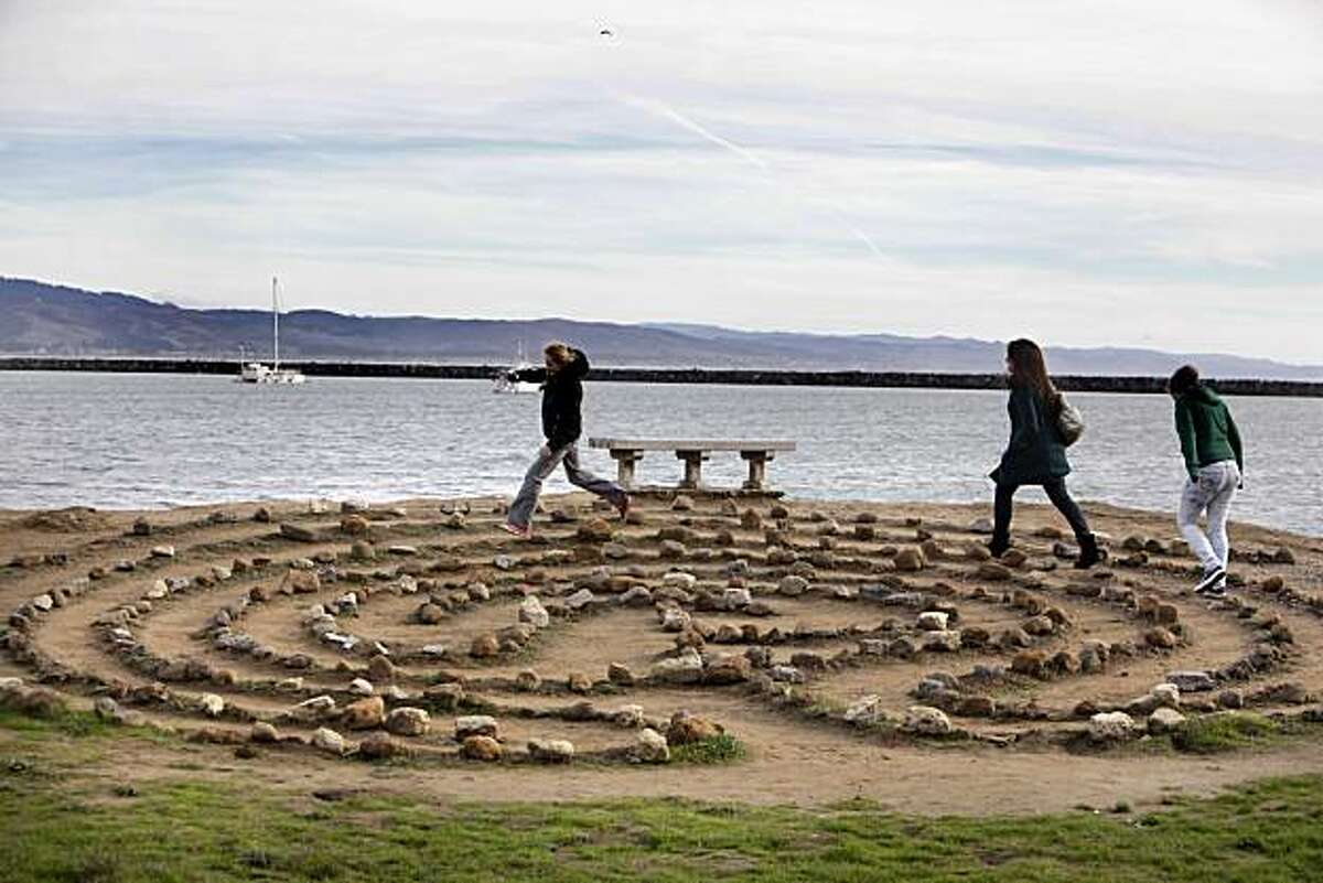 L-R, cousins, Kerry Walker, Katie Herskovitz, and Robin Walker, run around a labyrinth on the shore of Pillar Point Harbor near Half Moon Bay, Calif., on Friday, December 24, 2010. Urban Outings feature on Pillar Point, near Half Moon Bay. If you're tired of cold, gray Bay Area beaches with crashing waves, stroll out to sheltered, peaceful Pillar Point where gentle currents lap at a sandy beach and delicate clam shells crunch underfoot. Protected by Pillar Point Harbor, Pillar Point is part of the Fitzgerald Marine Reserve, which extends from the Montara light station south to Pillar Point.