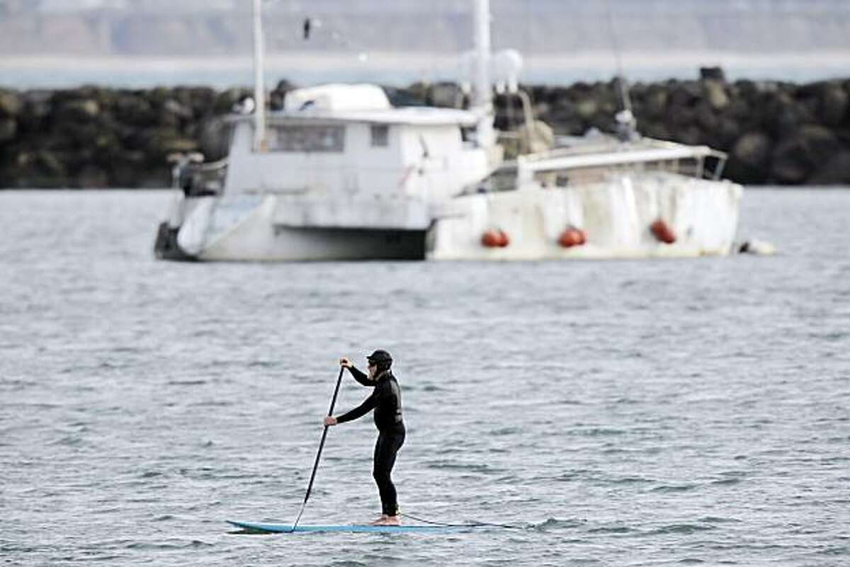 A paddle surfer makes his way through the calm waters of Pillar Point Harbor near Half Moon Bay, Calif., on Friday, Calif. Urban Outings feature on Pillar Point, near Half Moon Bay. If you're tired of cold, gray Bay Area beaches with crashing waves, stroll out to sheltered, peaceful Pillar Point where gentle currents lap at a sandy beach and delicate clam shells crunch underfoot. Protected by Pillar Point Harbor, Pillar Point is part of the Fitzgerald Marine Reserve, which extends from the Montara light station south to Pillar Point.