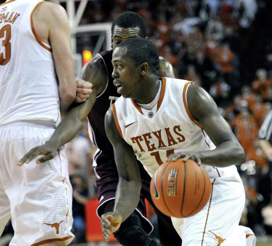 Texas guard J'Covan Brown drives around Texas A&M forward Khris Middleton during the second half of an NCAA college basketball game Wednesday, Jan. 11, 2012, in Austin, Texas. Texas won 61-51. (AP Photo/Michael Thomas) Photo: Michael Thomas, Associated Press / FR65778 AP