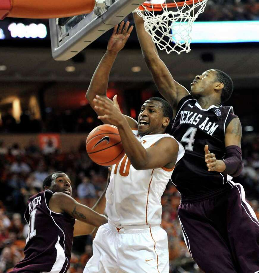 Texas guard Jonathan Holmes, center, tries to control the rebound against Texas A&M center Keith Davis, right, and Elston Turner, left, during the second half of an NCAA college basketball game Wednesday, Jan. 11, 2012, in Austin, Texas. Texas won 61-51. (AP Photo/Michael Thomas) Photo: Michael Thomas, Associated Press / FR65778 AP