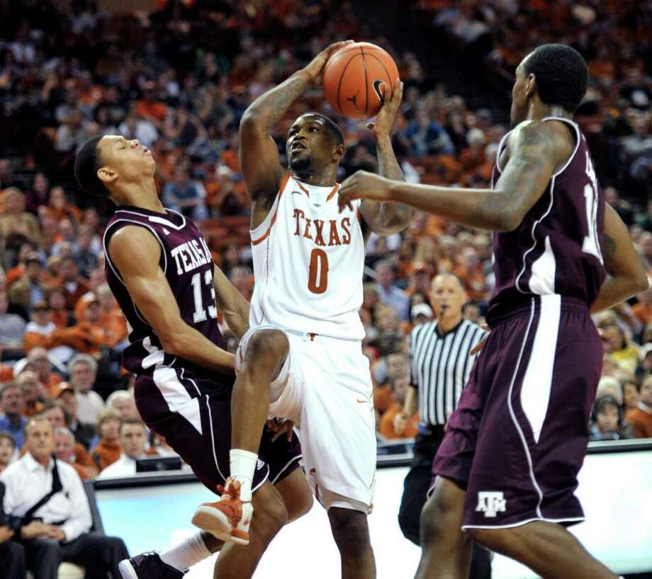 Texas guard Julien Lewis, center, goes up for a shot against Texas A&M guard Jordan Green, left, and center David Loubeau, right, during the second half of an NCAA college basketball game Wednesday, Jan. 11, 2012, in Austin, Texas. Lewis scored 16 points as Texas won 61-51. (AP Photo/Michael Thomas) Photo: Michael Thomas, Associated Press / FR65778 AP