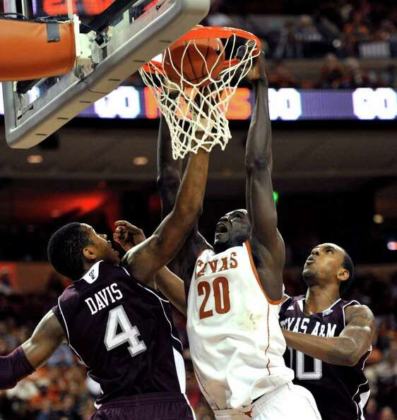 Texas forward Alexis Wangmene, center, dunks against Texas A&M's Keith Davis, left, and David Loubea