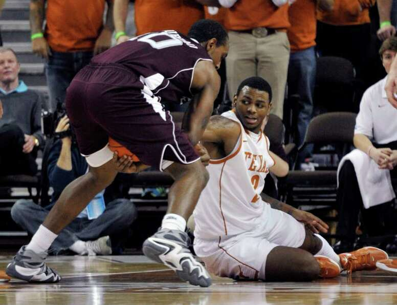 Texas guard Jaylen Bond, right, reaches for the loose ball against Texas A&M forward David Loubeau d