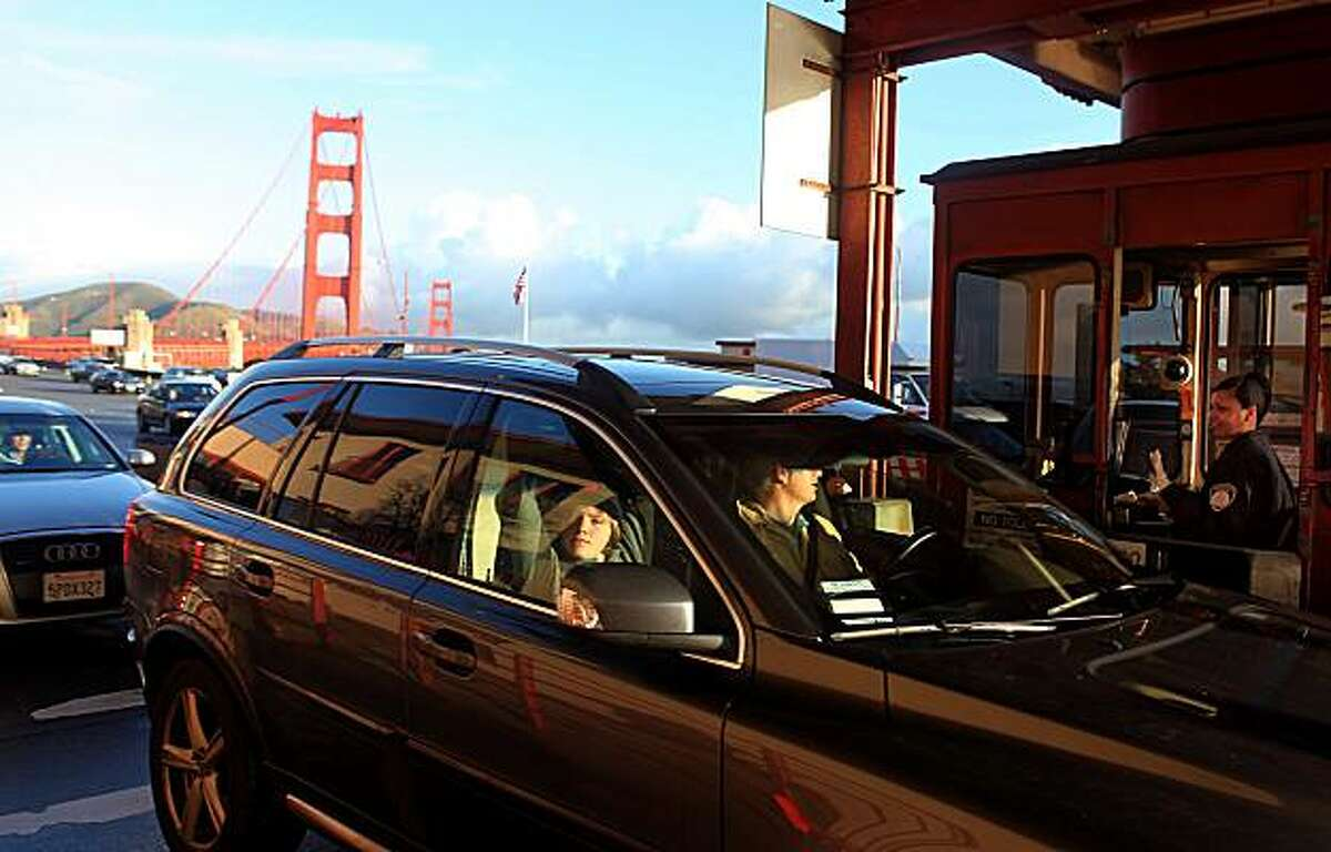 Bridge officer Shakira Upchurch waves a carpool through at the Golden Gate Bridge toll plaza in San Francisco, Ca., on Tuesday, February 9, 2010. The GG bridge may be placing tolls on carpoolers as early as this summer.