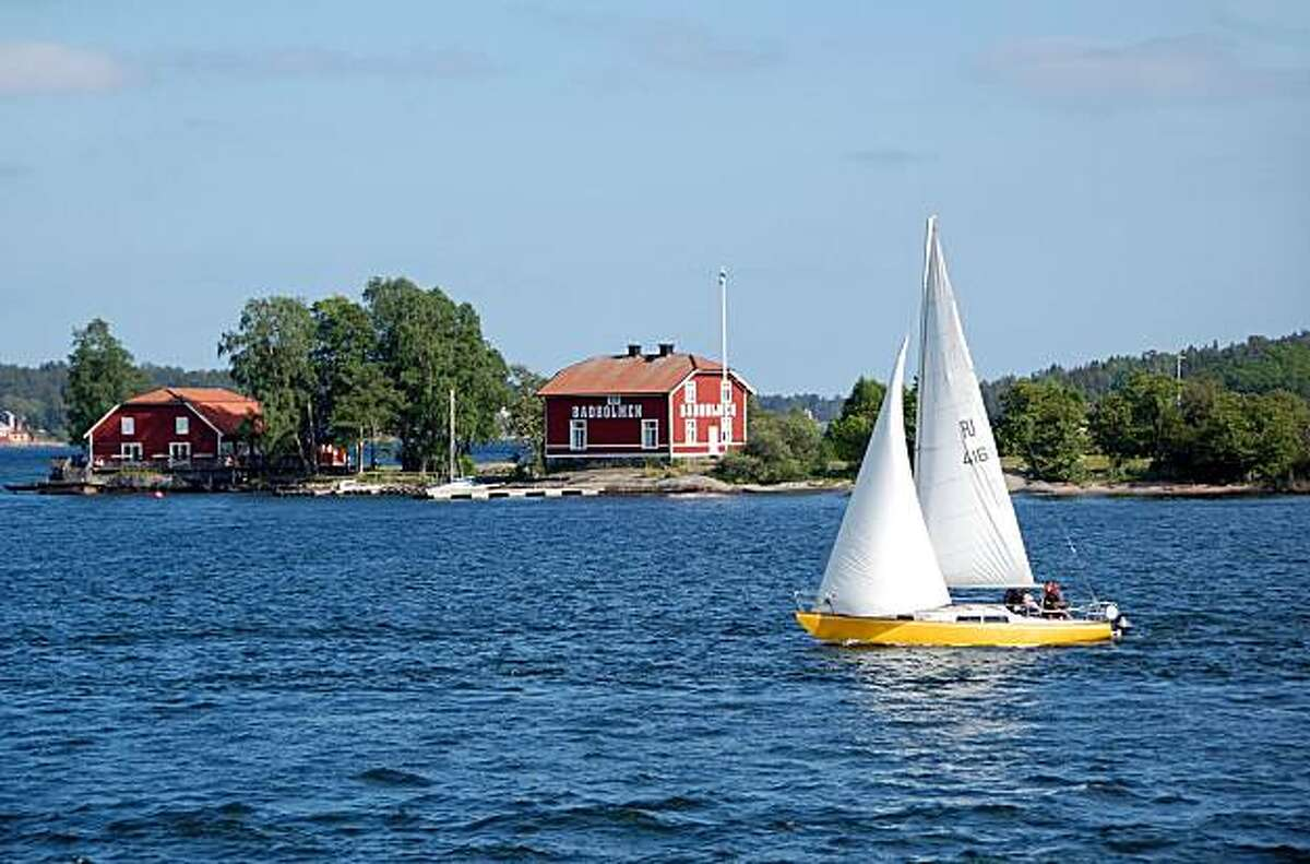 A sailboat zips by one of the tiny granite islands in Stockholm's archipelago.